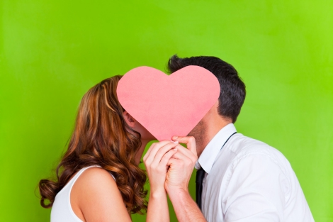 bigstock-Young-couple-kissing-behind-pr-19421999