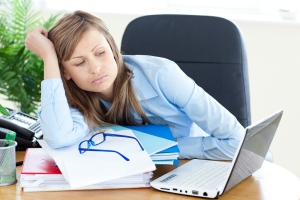 Stressed young businesswoman sitting at her desk in the office